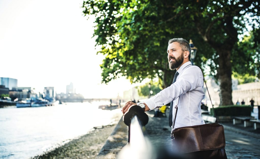 Hipster businessman with laptop bag standing by the river in London.