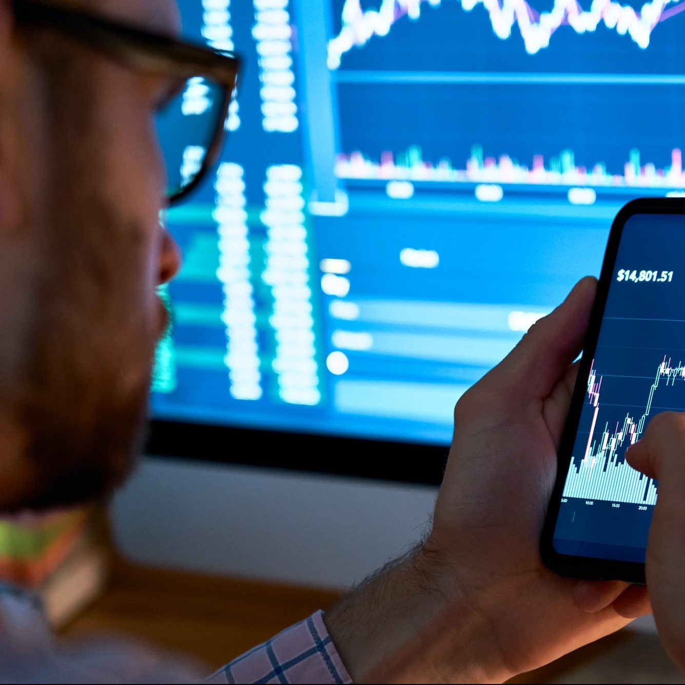 Trader using mobile phone app analytics for stock trading graph data analysis.